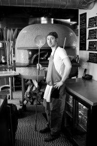 Picture of a man in t-shrit and jeans, standing in front of a wood fire oven