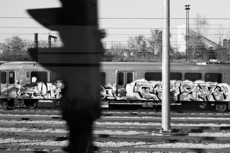 Picture of a light rail train with graffiti tags