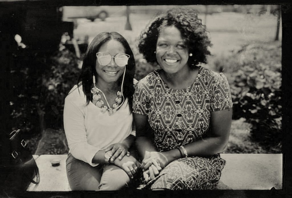 A picture of two women sitting down and smiling at the camera